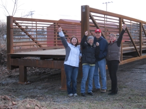 Ligonier Township Recreation Board members celebrate the arrival of the trail bridge to the Mill Creek location behind Weller Field. From left to right: Elizabeth McCall, President Sharon Detar, Larry Shew and Project Manager Rose Stepnick. (photo courtesy Rose Stepnick)